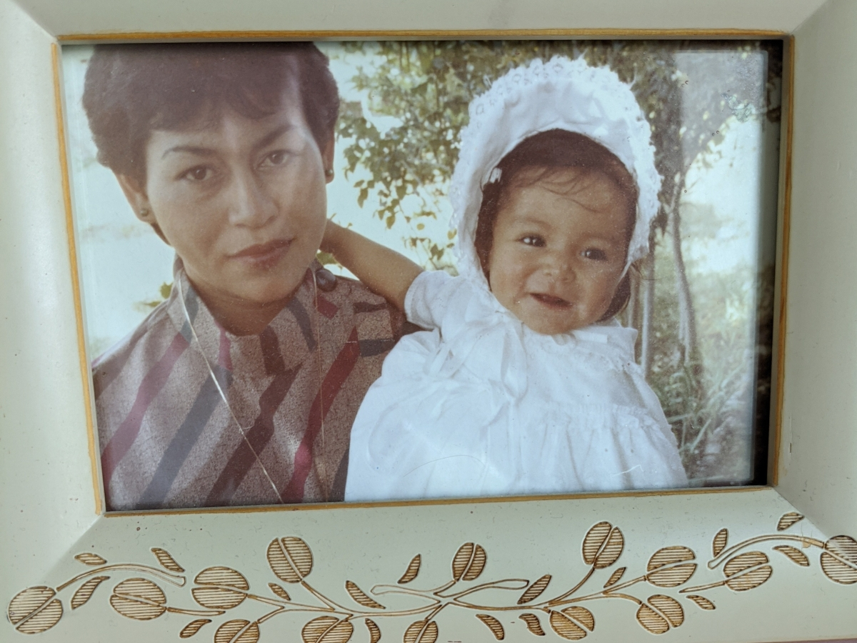 A photo of my guest Alejandra, as a baby with her mother Esperanza. She's wearing a white bonnet and gown, and smiling. Her mother is wearing a striped blouse and looking straight into the camera.